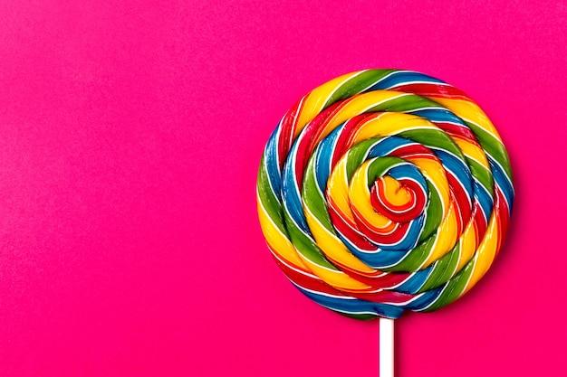 Sabroso apetitoso partido accesorio sweet swirl candy lollypop sobre fondo rosa vista superior