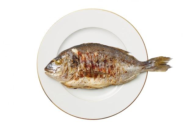 Sabroso apetitoso pescado frito dorado se encuentra en un plato blanco