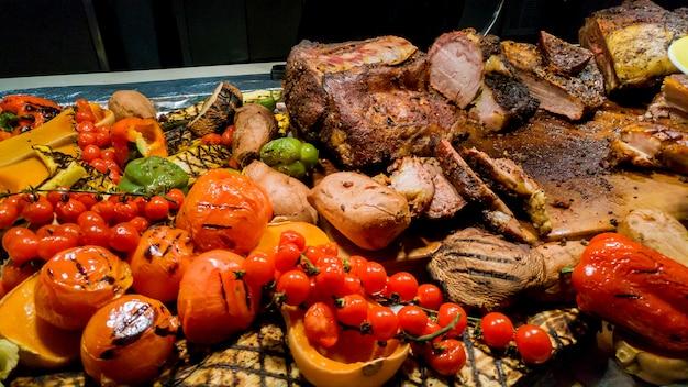 Sabroso bistec de barbacoa con tomate, chile y cebolla en el primer plano de la sartén de la parrilla sobre la mesa