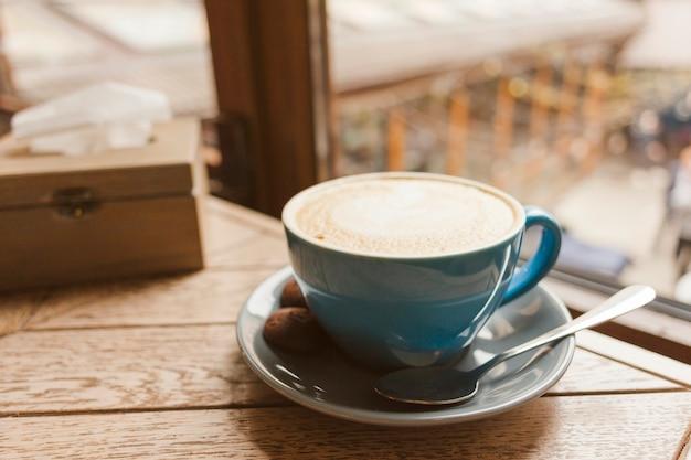 Sabroso café con deliciosas galletas en mesa de madera