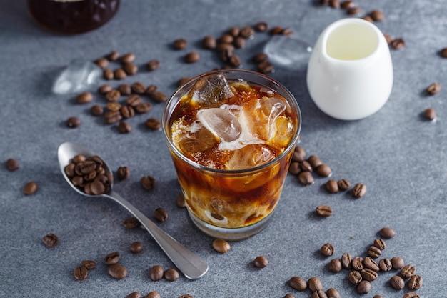 Sabroso café helado refrescante con cubitos de hielo en vasos sobre fondo brillante. de cerca