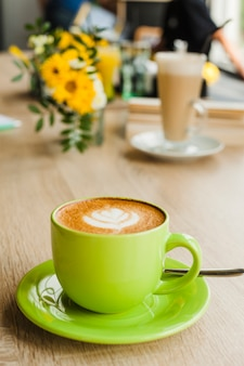 Sabroso café con leche con latte art en taza verde en el restaurante