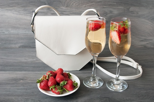 Sabroso champán en copas y fresas frescas