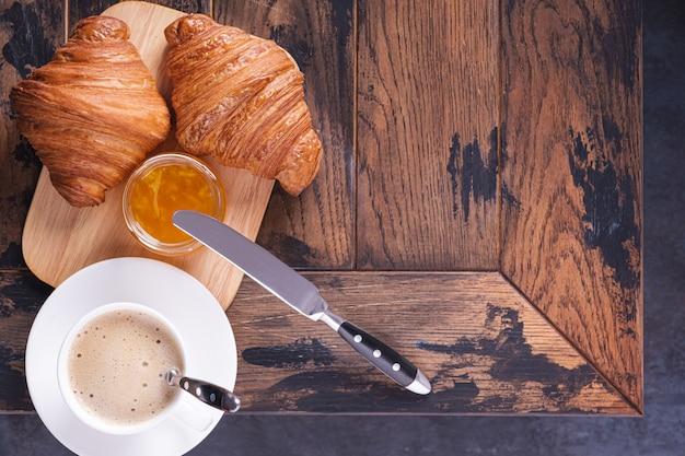 Sabroso croissant clásico y capuchino de café en la mesa