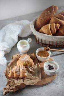 Sabroso desayuno con croissant francés, con un tazón de miel y crema. pasteles frescos de cerca.