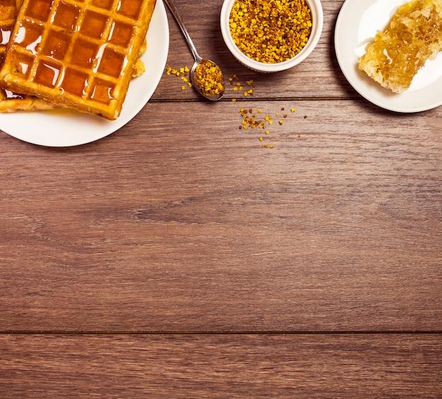 Sabroso desayuno con gofres; dulce miel y polen de abeja sobre escritorio de madera
