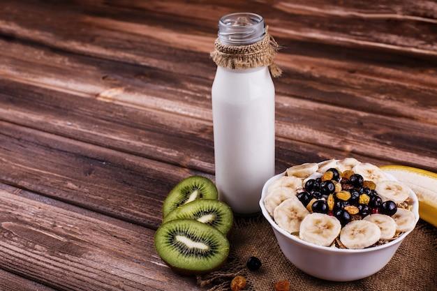 Sabroso desayuno saludable por la mañana hecho de leche y gachas de avena con nueces, kiwis y miel