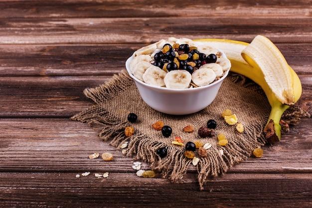 Sabroso desayuno saludable por la mañana hecho de leche y gachas con nueces, plátanos y miel
