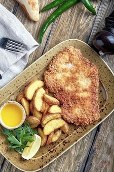 Sabroso escalope con patata hervida. vista superior, comida plana