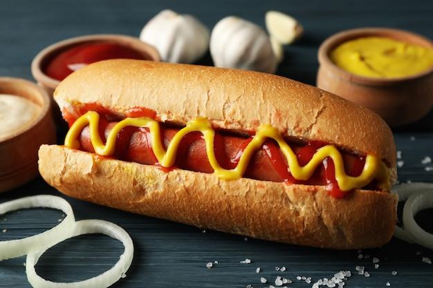 Sabroso hot dog e ingredientes en madera