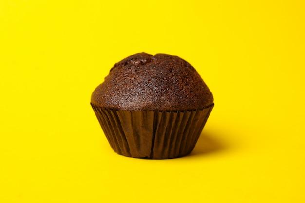 Sabroso muffin de chocolate sobre fondo amarillo, de cerca