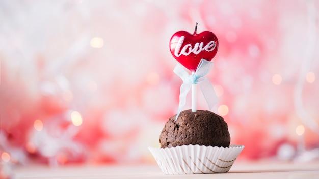 Sabroso muffin con vela encendida en varita