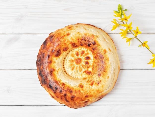 Sabroso pan tandoor redondo fresco sobre una mesa de madera blanca