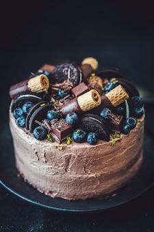 Sabroso pastel de chocolate casero fresco decorado con dulces y galletas servido en un plato