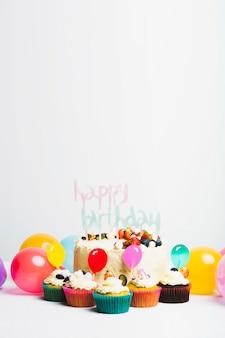 Sabroso pastel fresco con frutos rojos y título de feliz cumpleaños cerca de un juego de magdalenas y globos