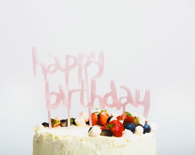 Sabroso pastel fresco con frutos rojos y título de feliz cumpleaños.