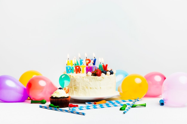 Sabroso pastel con frutos rojos y título de feliz cumpleaños cerca de globos de colores