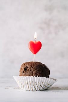Sabroso pastel con vela encendida en la varita