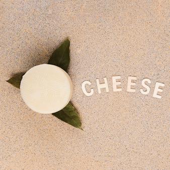 Sabroso queso manchego español sobre hojas de laurel con texto de queso sobre fondo de mármol
