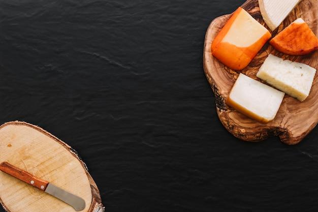 Sabroso queso y un pequeño cuchillo en la madera