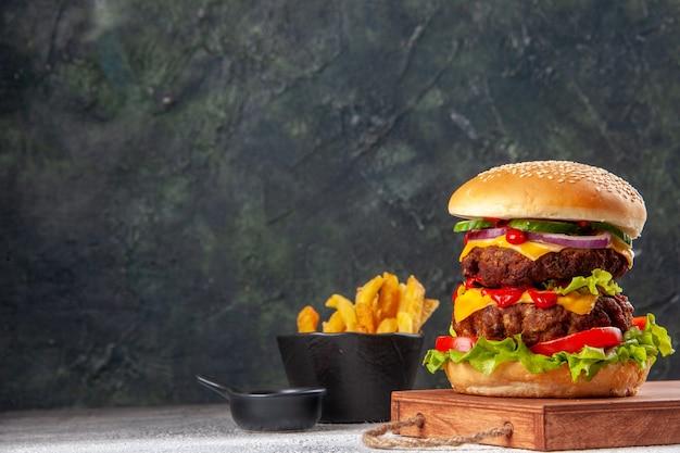 Sabroso sándwich casero en tabla de cortar de madera papas fritas en el lado izquierdo en la superficie borrosa