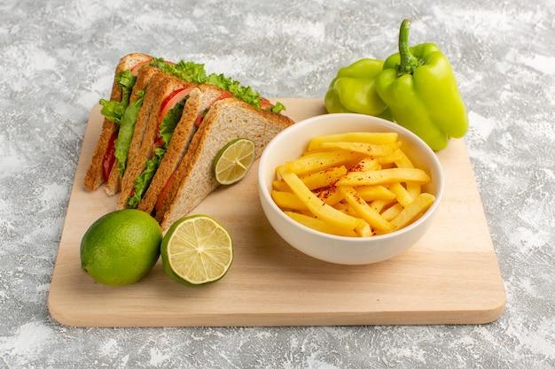 Sabroso sándwich junto con papas fritas limón y pimiento verde