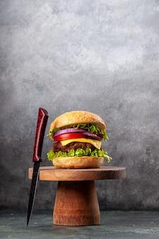 Sabroso sándwich y tenedor rojo sobre tablero de madera sobre una superficie de color oscuro mezclado con espacio libre