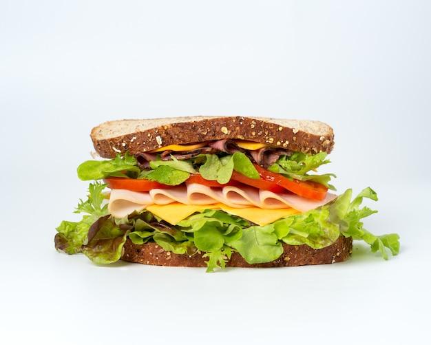 Sabroso sándwich con verduras, jamón y queso.