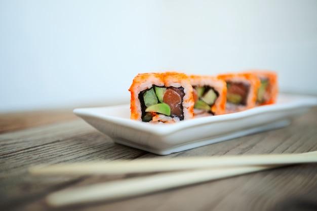 Sabroso sushi con palillos, mariscos japoneses tradicionales