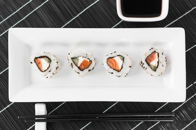 Sabroso sushi tradicional en bandeja blanca con salsa y palillos.