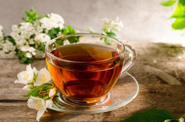 Sabroso té fragante con flor de jazmín. taza de té de cristal en una vieja mesa de madera. bebida caliente con flores de philadelphus.