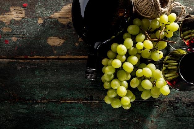 Sabroso vino tinto fresco en vidrio con uva y botella de vino