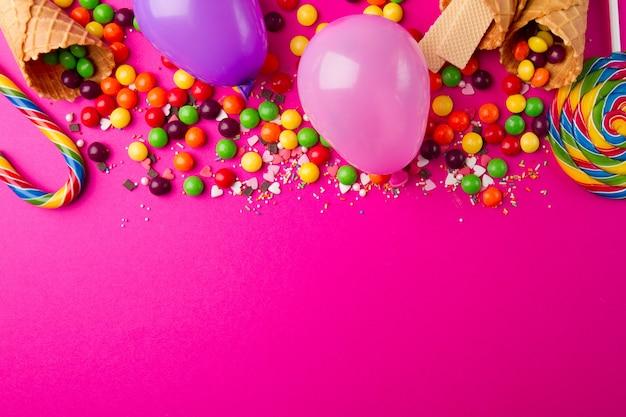 Sabrosos apetitosos accesorios de fiesta sobre fondo rosa brillante