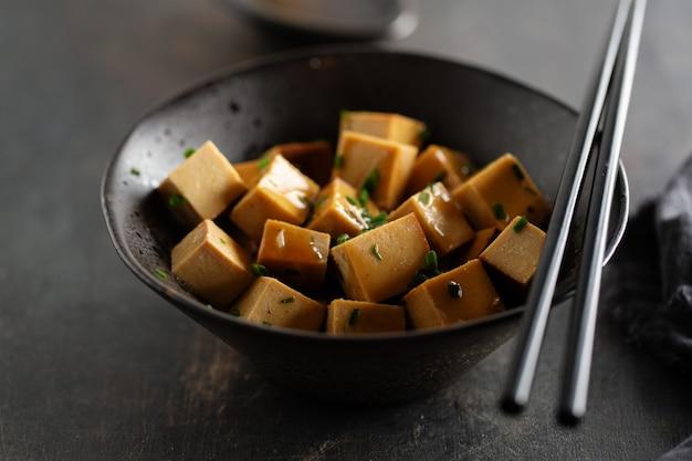 Sabrosos apetitosos trozos de tofu con salsa servida en un recipiente listo para comer. de cerca.
