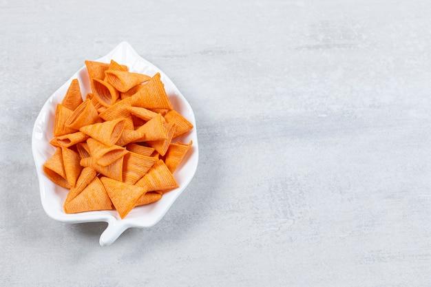 Sabrosos chips triangulares en placa en forma de hoja.