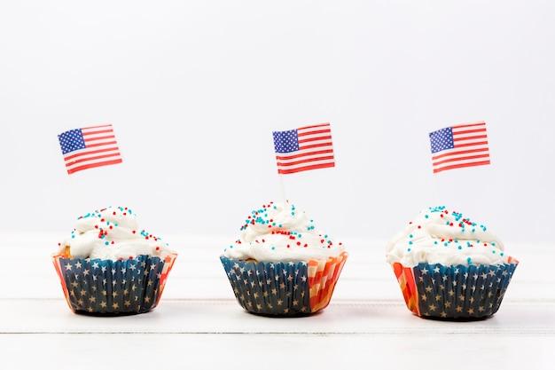 Sabrosos cupcakes de crema batida con banderas americanas.