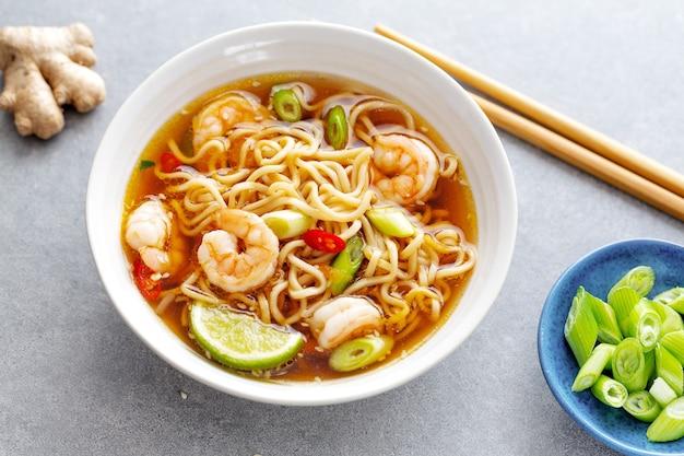 Sabrosos fideos asiáticos apetitosos con verduras y camarones en un recipiente sobre una superficie de hormigón