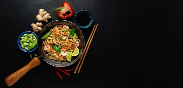 Sabrosos fideos asiáticos apetitosos con verduras y camarones en una sartén sobre una superficie oscura