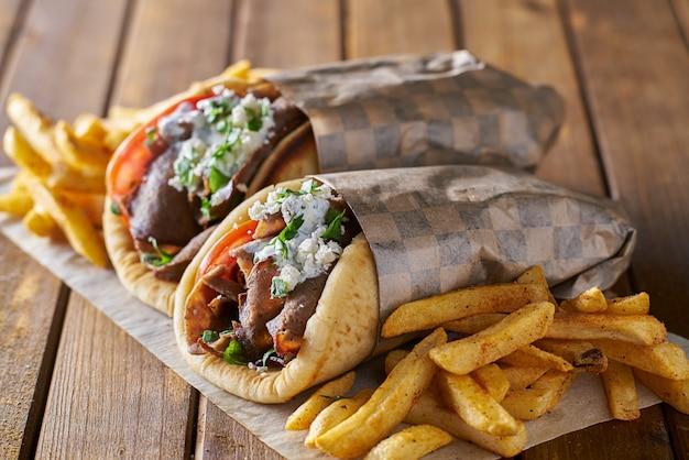 Sabrosos gyros griegos con patatas fritas con queso feta y salsa tzattziki