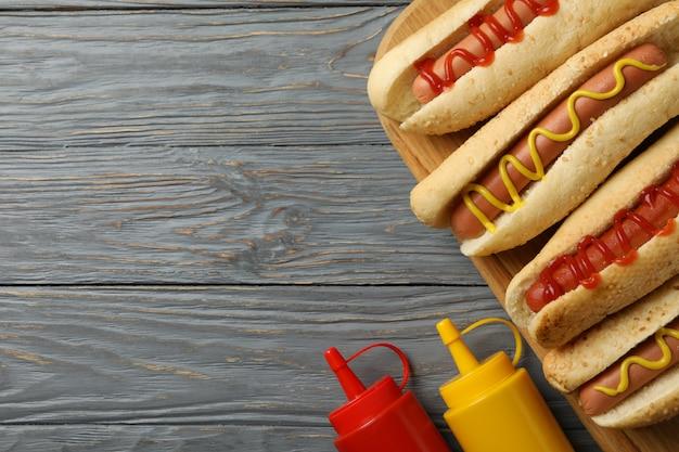 Sabrosos hot dogs y salsas en madera gris