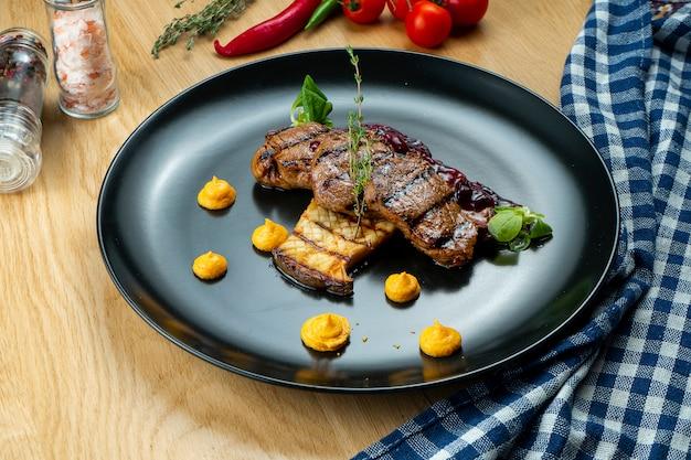 Sabrosos medallones de ternera a la parrilla con salsa de bayas y berenjenas en un elegante plato negro. restaurante que sirve.