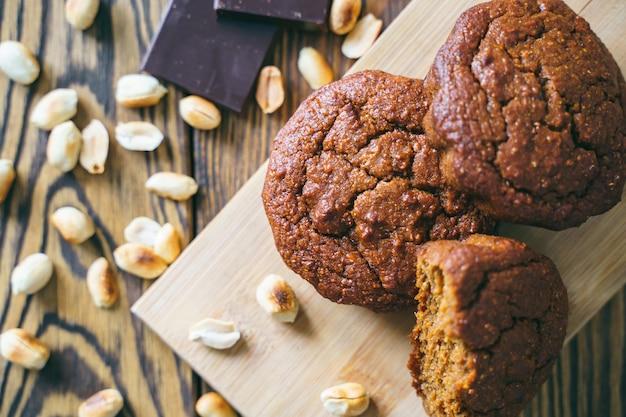 Sabrosos muffins de chocolate sobre una plancha de madera. pasteles dulces con chocolate y maní