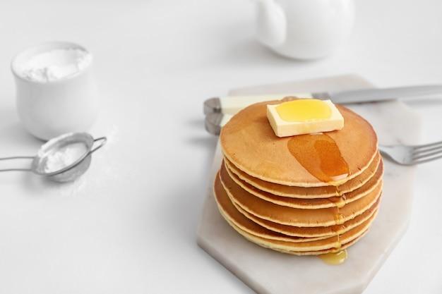 Sabrosos panqueques con mantequilla y miel en la mesa