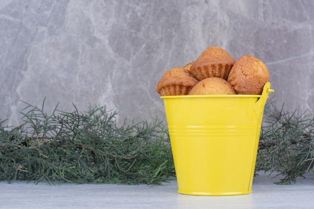 Sabrosos pasteles pequeños en cubo amarillo con rama de pino.