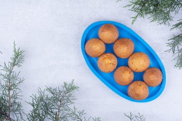 Sabrosos pasteles pequeños en placa azul con rama de pino.