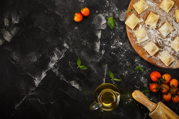 Sabrosos ravioles crudos con harina, tomates cherry, aceite de girasol y albahaca sobre una superficie oscura