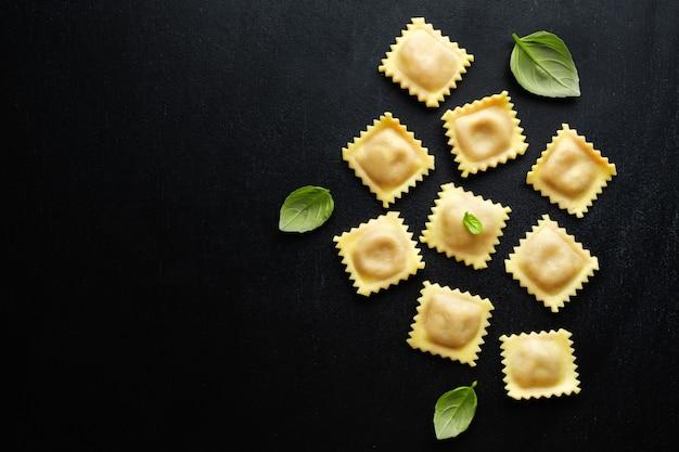 Sabrosos ravioles italianos clásicos con albahaca sobre fondo oscuro. vista superior.