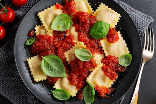 Sabrosos ravioles italianos cocidos con salsa de tomate y albahaca servidos en un plato oscuro.