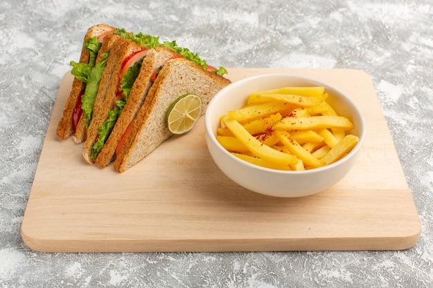 Sabrosos sándwiches junto con papas fritas en gris claro