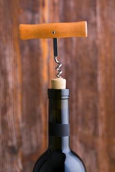 Sacacorchos de primer plano y cabeza de botella de vino con fondo borroso